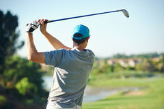 Golf shot man. Golfer hitting golf shot with club on course while on summer vacation stock image