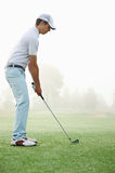 Golf shot man. Golfer hitting golf shot with club on course while on summer vacation royalty free stock image