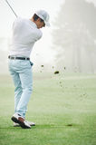 Golf shot man. Golfer hitting golf shot with club on course while on summer vacation royalty free stock photos