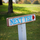 Golf Sign: Next Tee. A painted wooden sign that reads Next Tee on a golf course Royalty Free Stock Photos