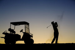 Golf Silhouette. A young man golfing at sunset Royalty Free Stock Images