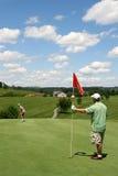 Golf - Sohn, der Kugel am Vater neigt Markierungsfahne setzt Lizenzfreie Stockfotos