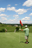 Golf - Son Putting Ball at Father Tending Flag Royalty Free Stock Photos