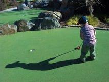Golf spielen des kleinen Jungen Lizenzfreie Stockfotos