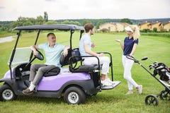 Golf spielende Begleiter auf Golfplatz Lizenzfreie Stockbilder