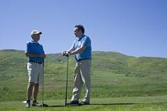 Golf spielende Freunde lizenzfreie stockbilder
