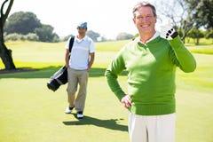 Golf spielende Freunde, die an der Kamera lächeln Lizenzfreie Stockfotos