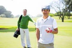 Golf spielende Freunde, die an der Kamera lächeln Stockbilder