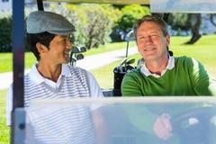 Golf spielende Freunde, die in ihrem verwanzten Lächeln des Golfs an der Kamera fahren Lizenzfreies Stockfoto