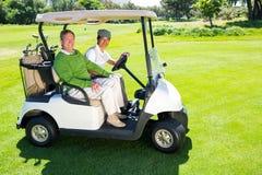 Golf spielende Freunde, die in ihrem verwanzten Lächeln des Golfs an der Kamera fahren Lizenzfreie Stockfotografie