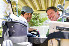 Golf spielende Freunde, die in ihrem verwanzten Lächeln des Golfs an der Kamera fahren Stockbilder