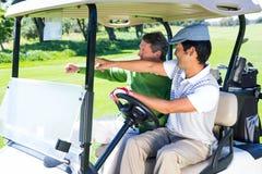 Golf spielende Freunde, die in ihren Golfbuggy fahren Stockfoto