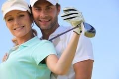 Golf spielende Paare Stockfoto