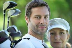 Golf spielende Paare Stockfotos