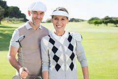 Golf spielende Paare, die an der Kamera auf dem Übungsgrün lächeln Lizenzfreies Stockbild