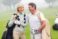 Golf spielende Paare, die Vereine lächeln und halten lizenzfreies stockbild