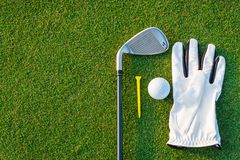 The golf sport equipment  white glove ,golf ball, golf club and  yellow tee golf with green grass. Background stock images