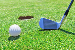 Golf stick  ball near the hole. Royalty Free Stock Image