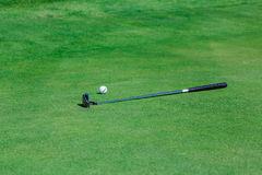 Golf stick and ball near the hole. Stock Image