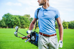 Golf is a style of living. Cropped image of male golfer carrying golf bag with drivers while walking by green grass Stock Images