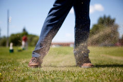 Golf Swing. A golf swing on a driving range with sand in the air Royalty Free Stock Image