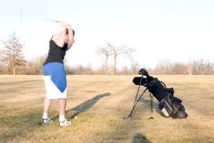 Golf Swing 2. A young man practising his golf swing with his equipment close by Stock Image