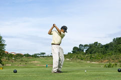 Golf Swing. A Chinese pensioner driving off the blue tee box Royalty Free Stock Photo