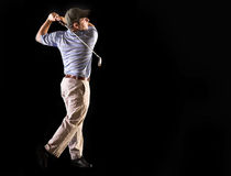 Golf swing isolated on black. Golfer looking at golf ball after swinging club Stock Photo