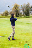 Golf swing. A golf player practicing the swing on the driving range Stock Image