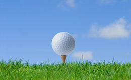 Golf on the tee. Golf ball on a tee with the blue sky and white clouds Royalty Free Stock Image