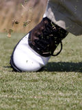 Golf tee flying after impact. Close up of flying broken golf tee, flying grass, and golfers shoe after hitting ball stock photo