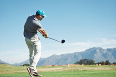 Golf tee shot. Golfer hitting tee shot with driver from teebox, on beautiful course and good strike Stock Image