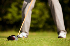 Golf teeing. Golf player attempting the tee stroke in the teeing area (only legs of player to be seen, focus on ball stock photography