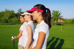 Golf three woman in a row green grass course Stock Photos