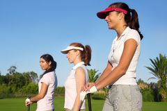 Golf three woman in a row green grass course Royalty Free Stock Photo