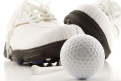 Golf time. Golf ball with shoes and tee Stock Image