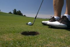 Golf about to putt. Close up of a man about to make a putt at a golf hole Royalty Free Stock Photography