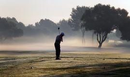 Golf tournament. A man prepares to hit the ball on a foggy morning during a companies golf tournament in the spanish island of mallorca Stock Photos