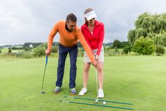 Golf trainer helping the female player. Young female golf player at driving range with a golf coach stock photography