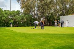 Golf trainer working with golf player on driving range. Malaga, Spain - April 07, 2018. Golf trainer working with golf player on driving range Stock Images