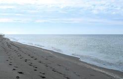 Golf van de wolken van Mexico en strandvoetafdrukken na zonsopgang Royalty-vrije Stock Afbeelding