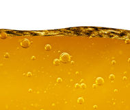 Golf van een gele vloeistof met luchtbellen op witte achtergrond Stock Afbeeldingen