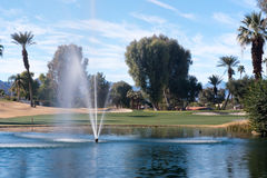 Golf water hazard with a fountain and trees Stock Images