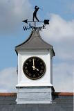 Golf Weather Vane. With white clock tower beneath with time set at four o'clock. Set against a blue sky and clouds royalty free stock photo