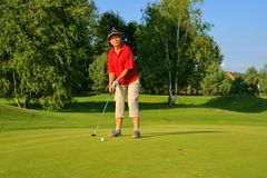 Golf, woman golfer thrusting the ball into the hole Stock Photos