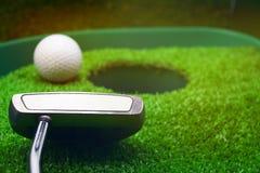 Golf y con el putter en fondo verde fotos de archivo