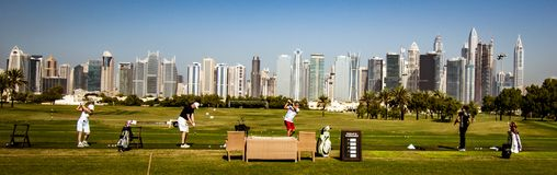 Golfare övar på körningsområde med Dubai horisont i baksidan Arkivbilder
