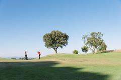 Golfare och caddie som spelar golf Arkivbilder