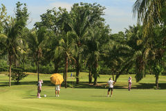 Golfare och caddier på golfbana i Thailand Fotografering för Bildbyråer