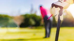 Golfare räcker och handsken som lutar på en golfklubb royaltyfria bilder